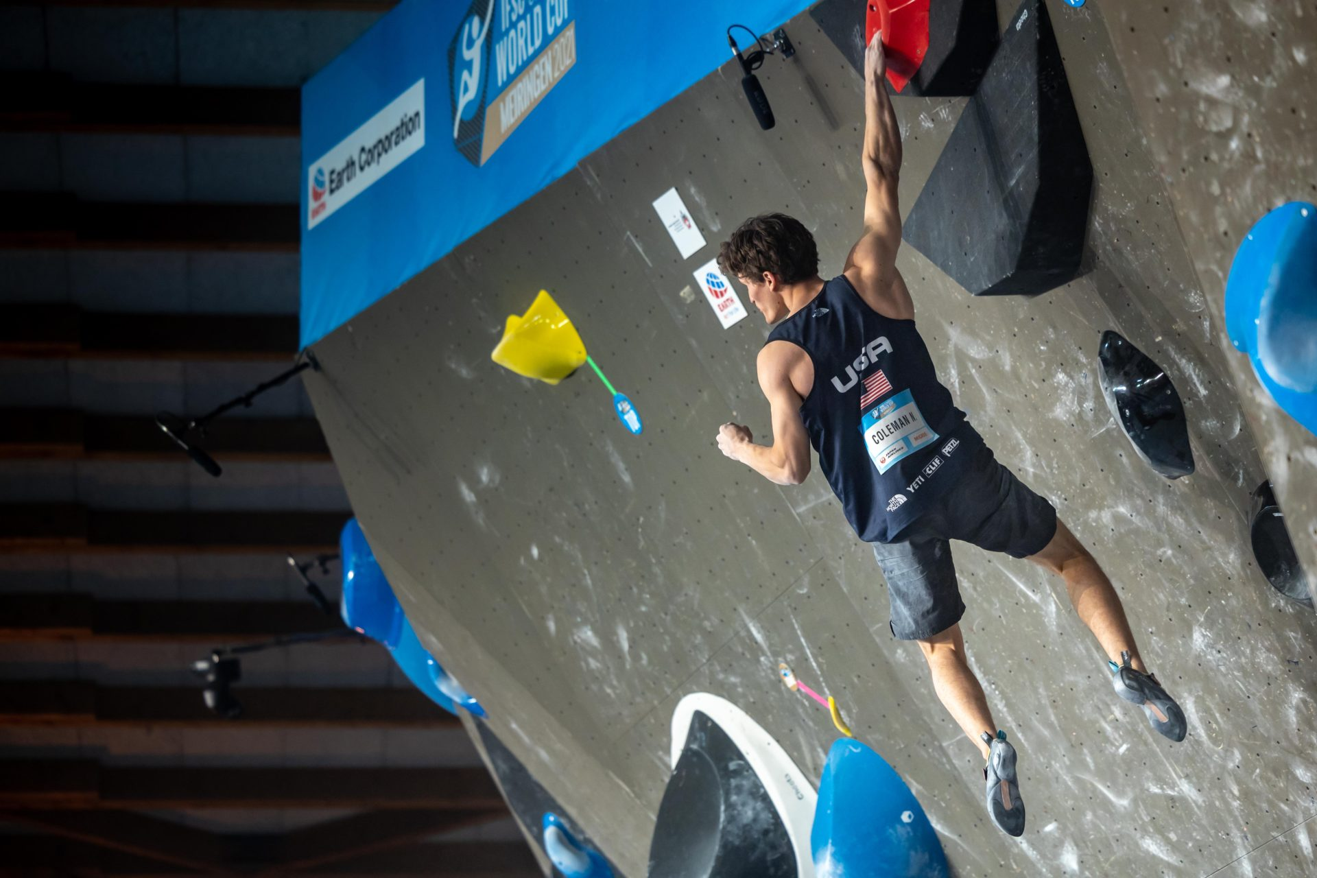 USA Climber Coleman hanging on wall with one arm