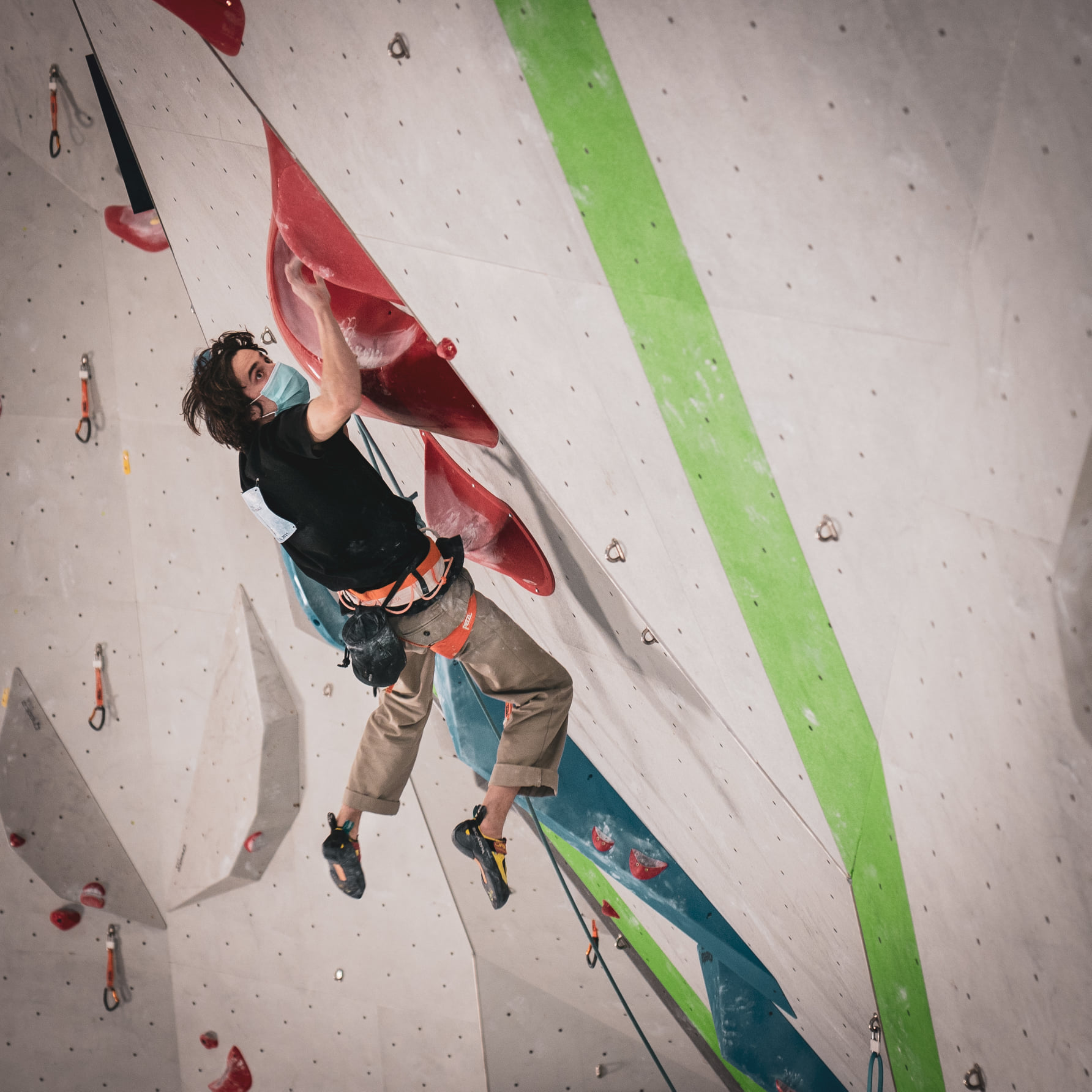 Male competitor mid jump on climbing wall