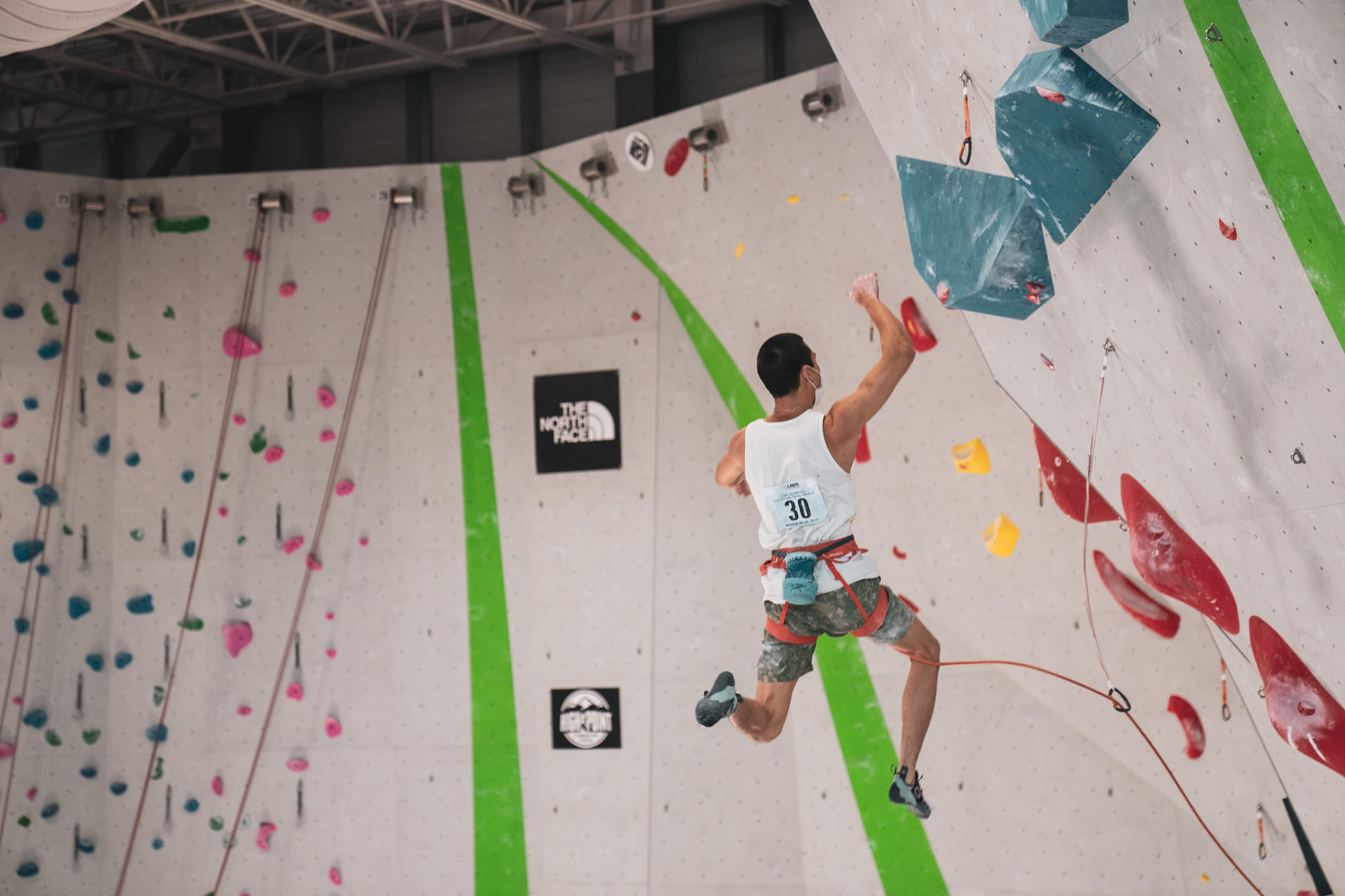 #30 Male climbing competitor mid jump on climbing wall
