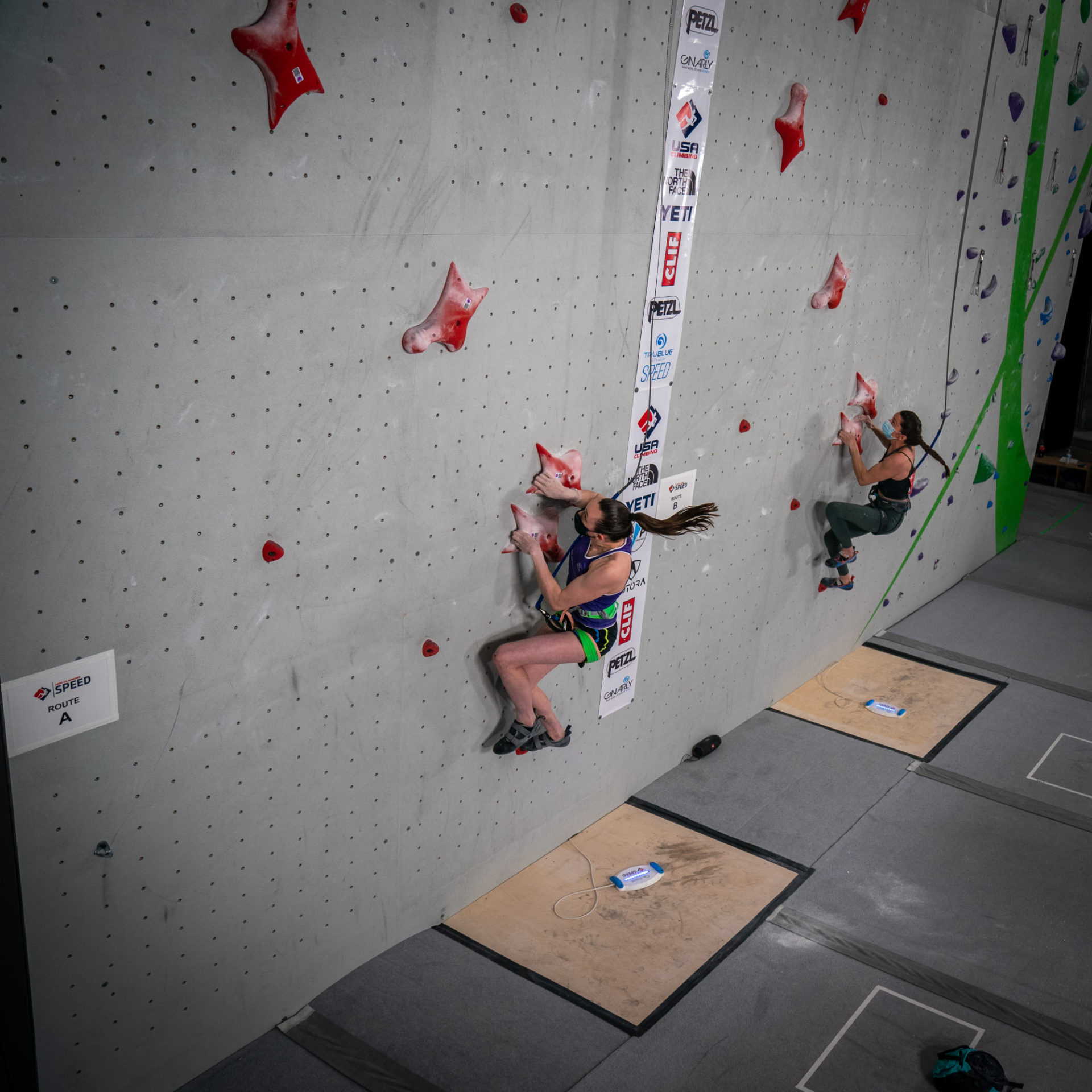 Two female competitors side by side on climbing wall