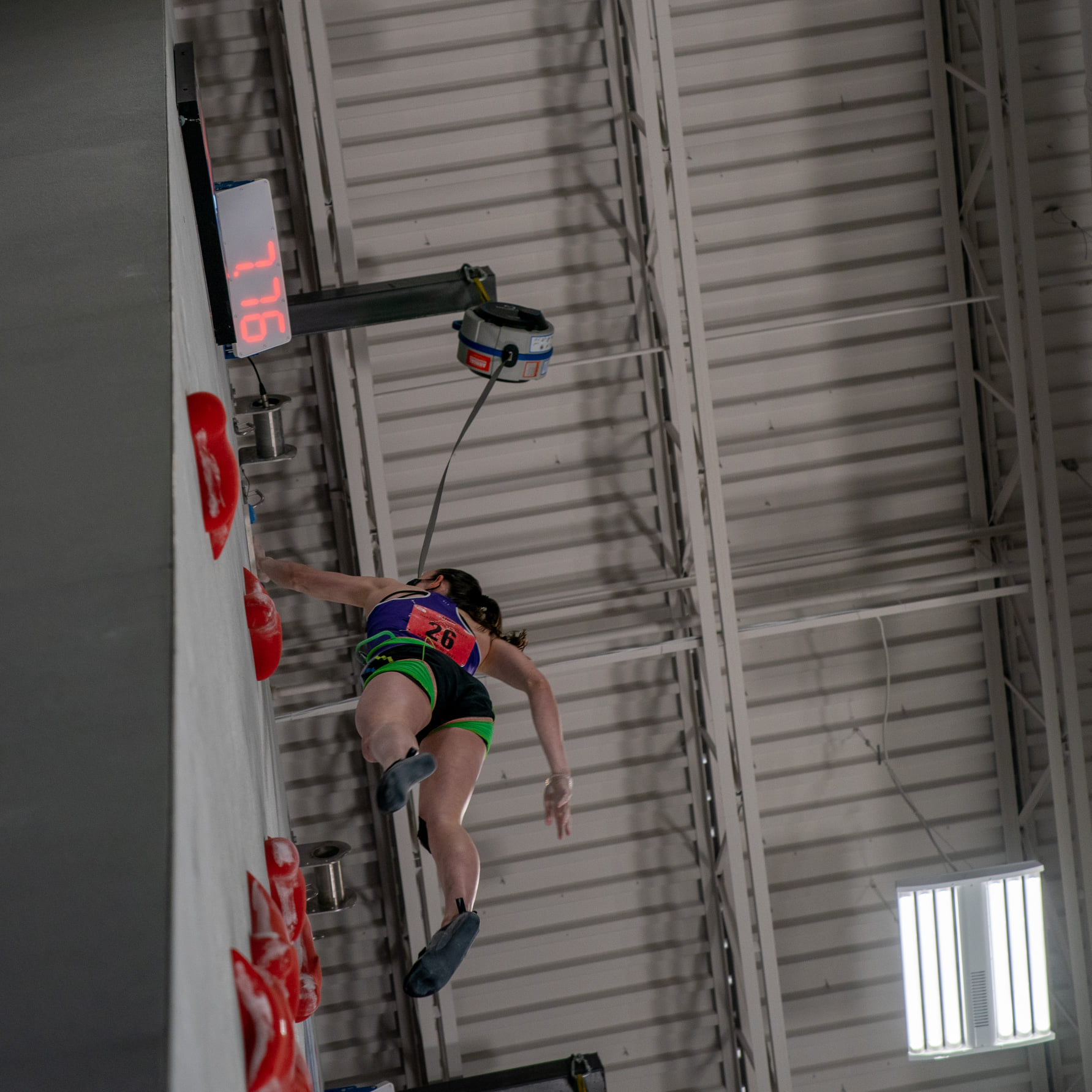 Female competitor at the top of the climbing wall