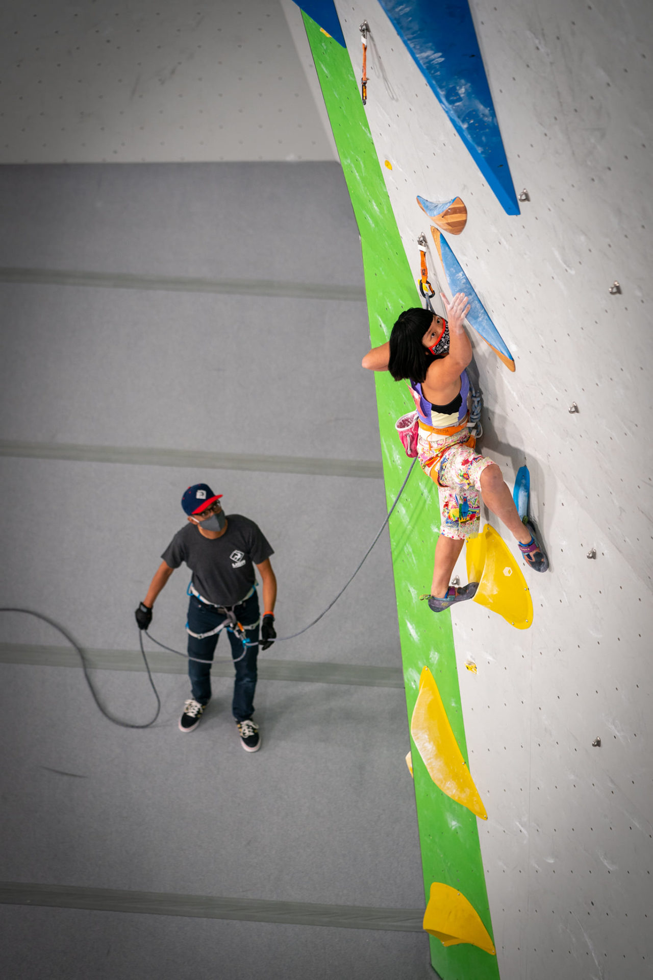 Male staff member belaying youth athlete on climbing wall