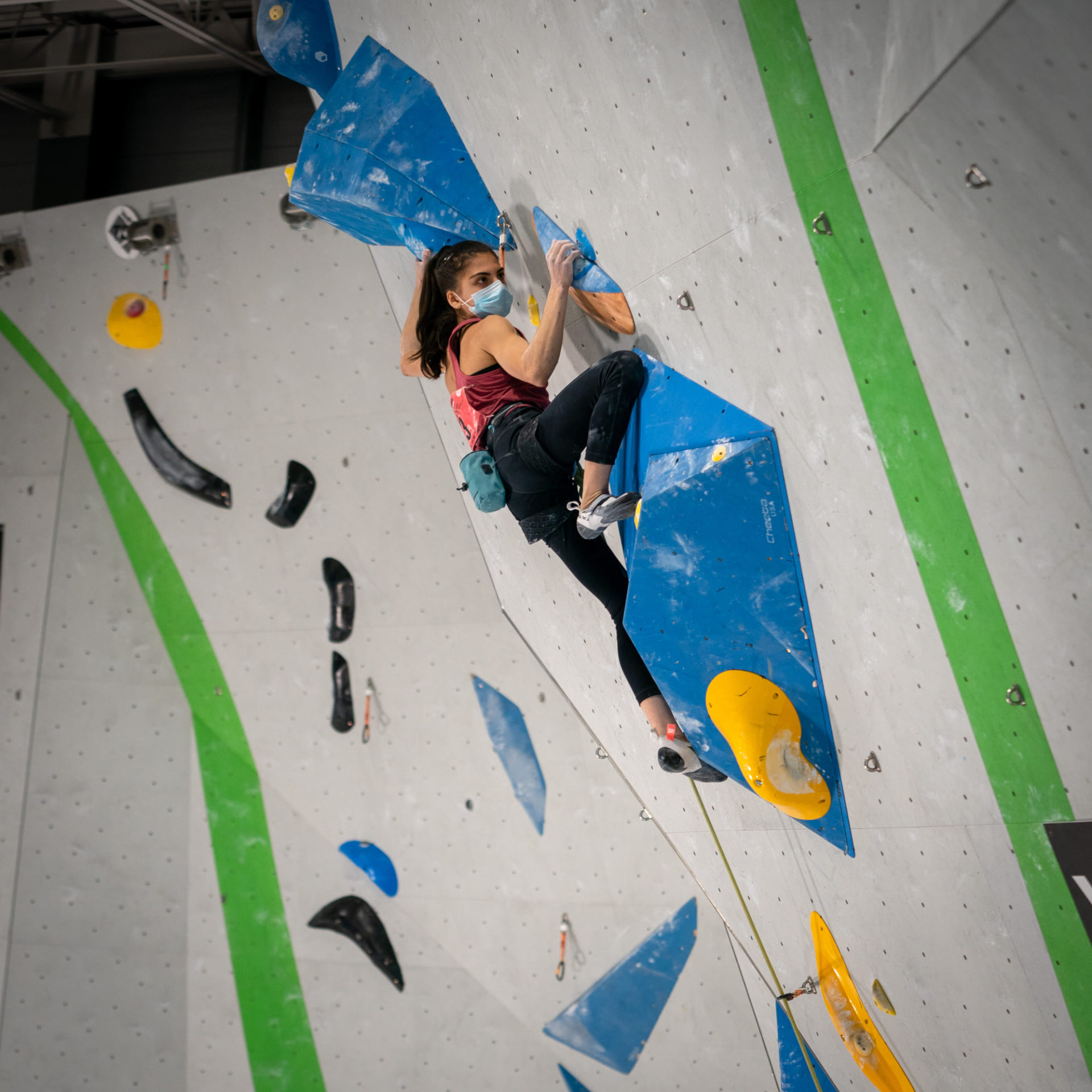 Female climbing competitor on wall