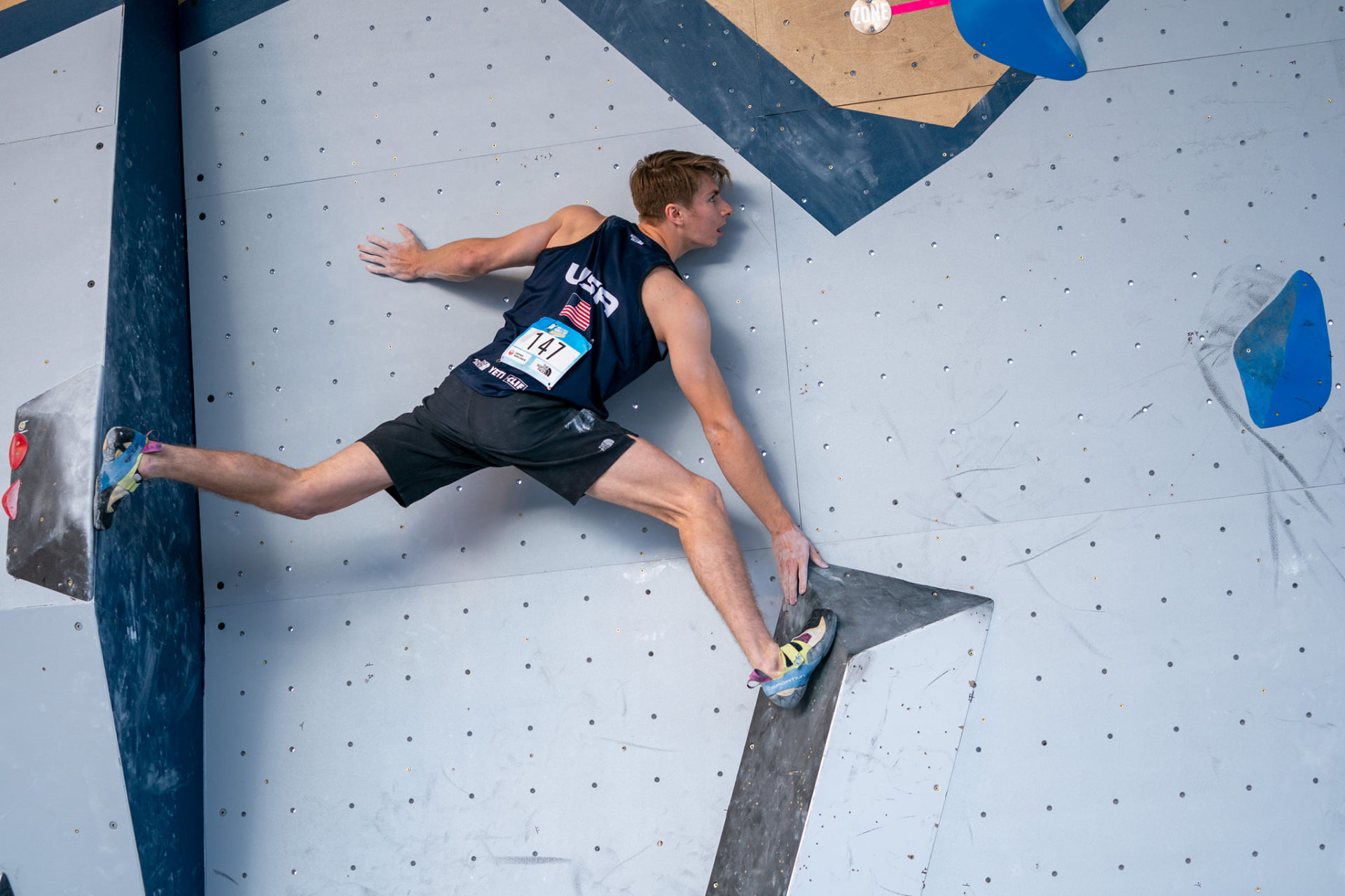 Male USA Climber #147 mid lunge on climbing wall