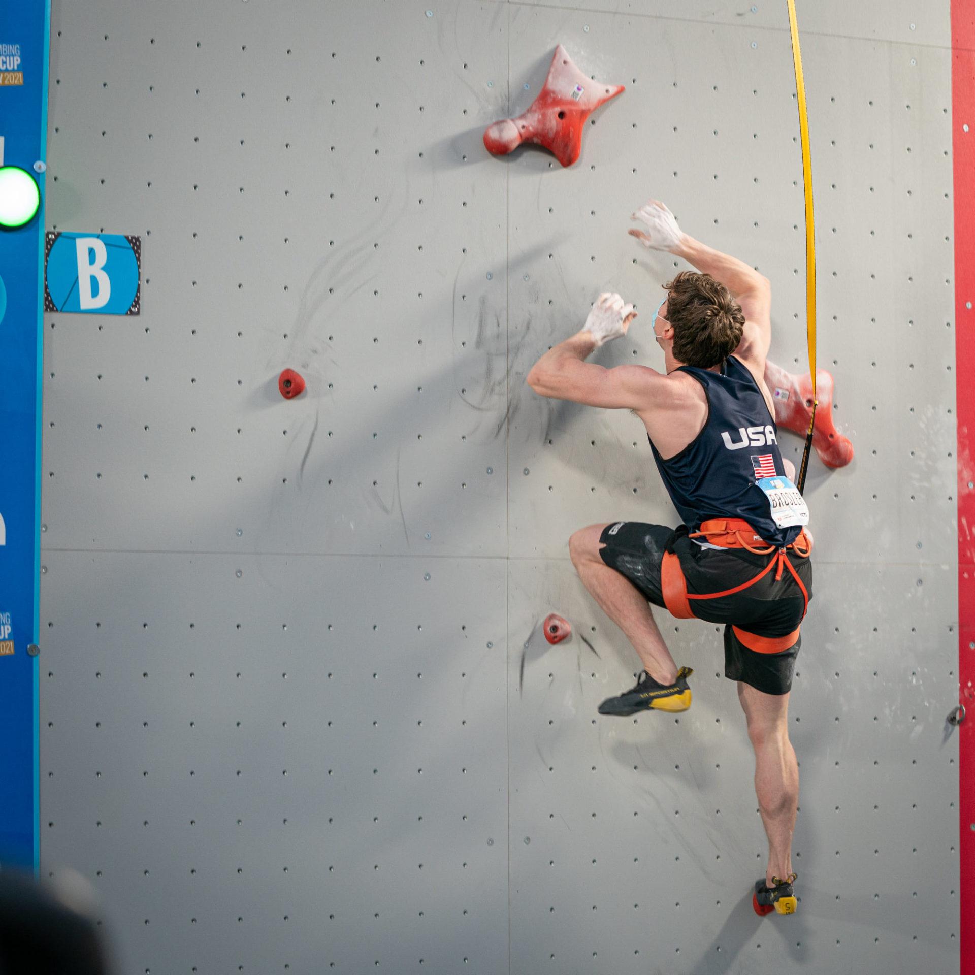 USA Male climber on climbing wall mid reach