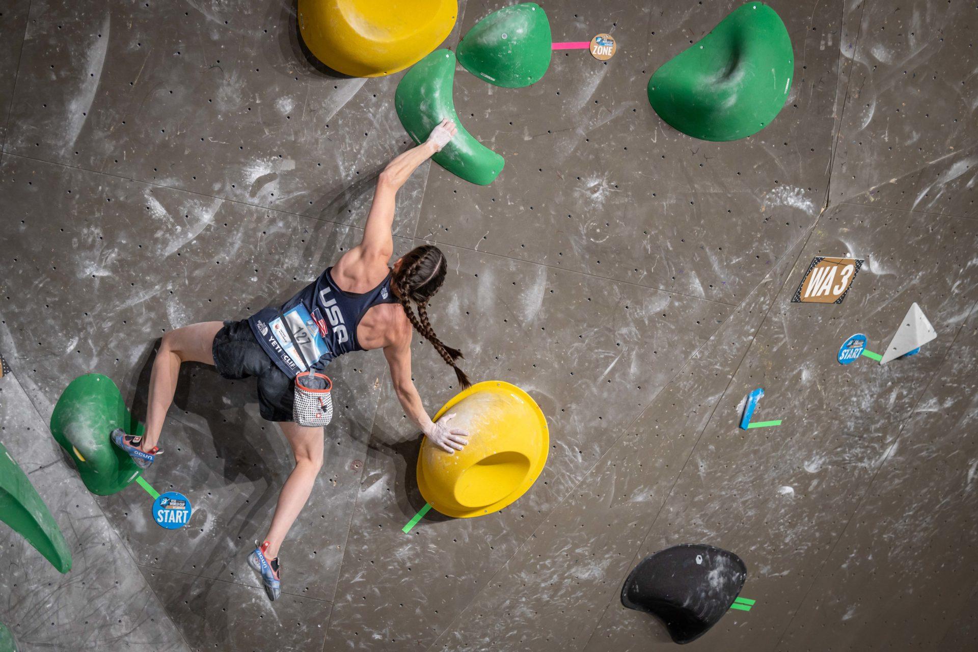 Female USA Climber #127 mid reach on climbing wall