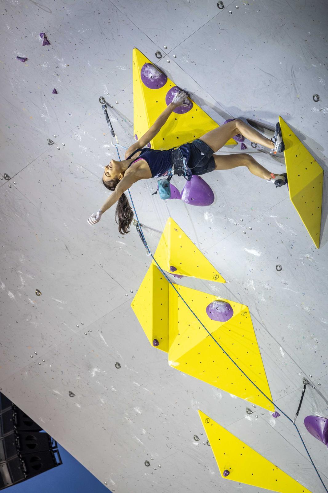 Female USA Climber hanging on climbing wall