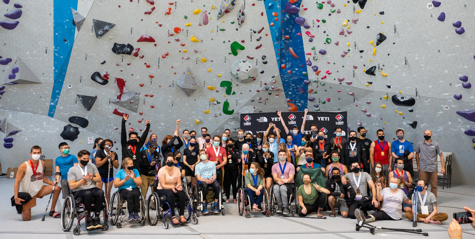 Paraplegic group photo in front of climbing wall
