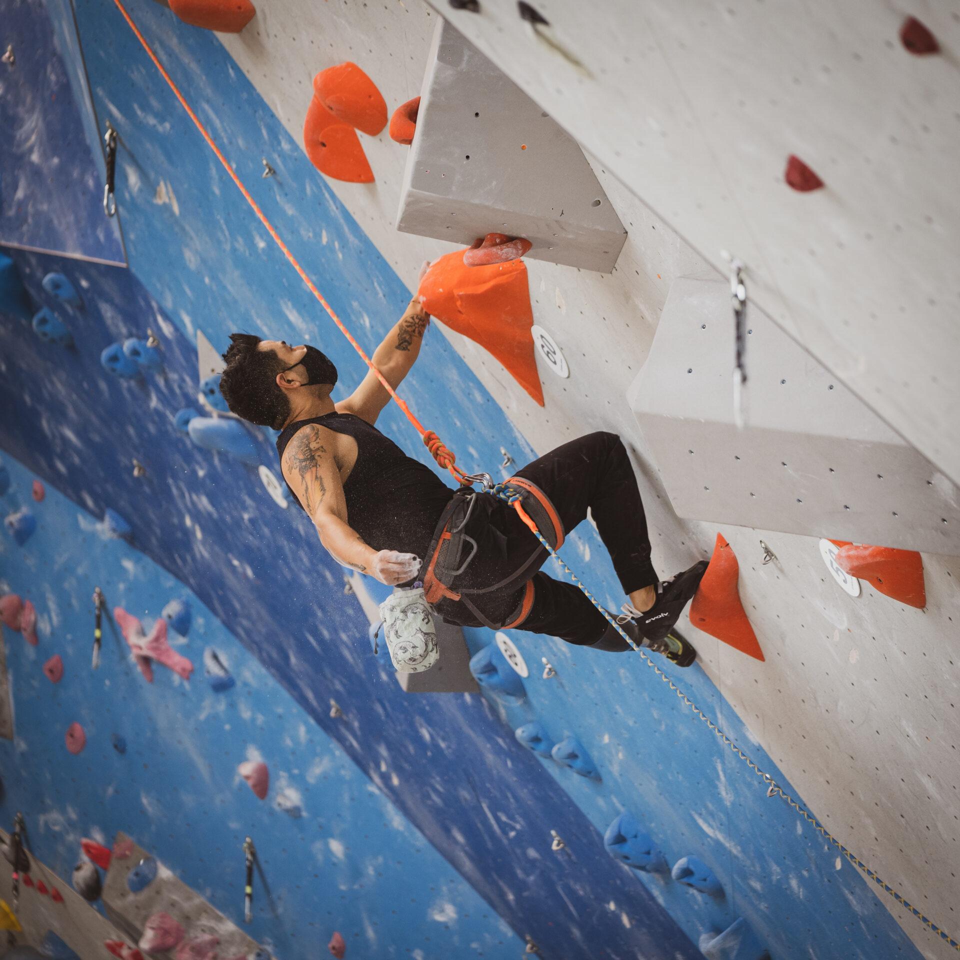 Jake Sanchez, US Paraclimbing National Team, climbs high on a lead wall.